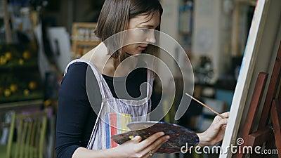 Muchacha joven del pintor en el delantal todavía que pinta la imagen de la vida en lona en arte-clase almacen de video