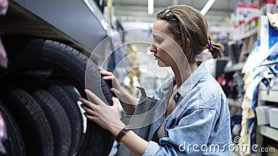 Muchacha linda en el centro comercial grande que selecciona los neumáticos del coche examinación comprador Filas de diversos neum metrajes