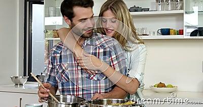 Muchacha linda que abraza a su novio mientras que él está cocinando almacen de metraje de vídeo