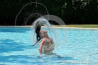 Muchacha o mujer en la piscina que lanza el pelo mojado detrás