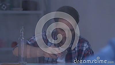 Muchacha olvidada que se sienta cerca de la ventana, vodka de consumición del padre adicto del alcohol almacen de metraje de vídeo