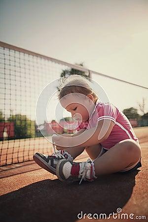 Muchacha que aprende atar cordones