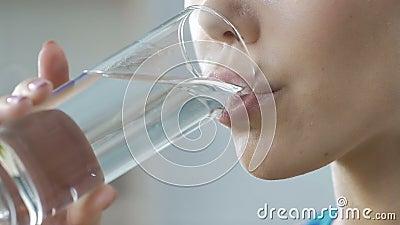 Muchacha que bebe el vidrio de agua mineral fresco limpio, balanza del cuerpo de la aguamarina, hidración almacen de video