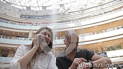 Muchacha que habla en el teléfono, y los puntos del individuo con el reloj en el fondo de la fuente en la alameda almacen de metraje de vídeo