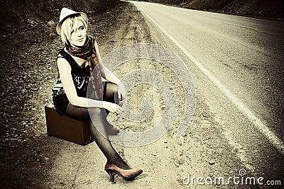 Muchacha que hace autostop con la maleta
