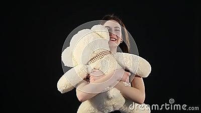 Muchacha que juega con el oso de peluche - aislado en negro almacen de video
