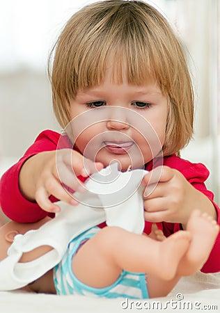 Muchacha que juega con su muñeca