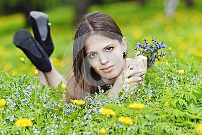 Muchacha que miente en una hierba con un manojo de flores