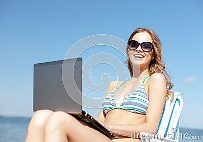 Muchacha que mira la PC de la tableta en la playa