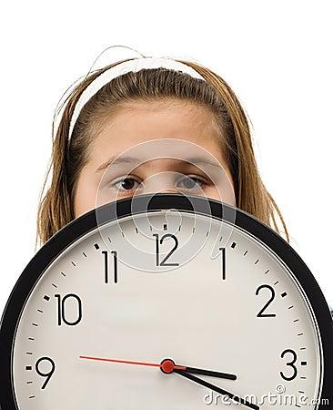 Muchacha que oculta detrás del reloj