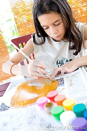 Muchacha que pinta una placa de papel con la pintura de cartel