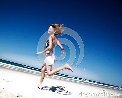 Muchacha que se ejecuta abajo de la playa