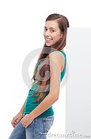 Muchacha que se inclina contra el cartel en blanco