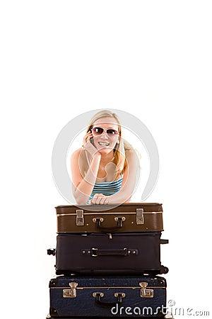 Muchacha que se inclina en las maletas