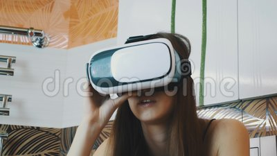 Muchacha que se sienta en cuarto de baño con la máscara de la realidad virtual en la cabeza Mirada alrededor almacen de metraje de vídeo