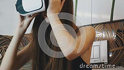 Muchacha que se sienta en cuarto de baño en vidrios de la realidad virtual en la cabeza Mirada alrededor almacen de video