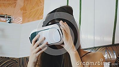 Muchacha que se sienta en el cuarto de baño que mira en vidrios de la realidad virtual Adminículo moderno metrajes