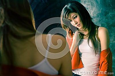 Muchacha que tiene enfermedad del insomnio delante de un espejo