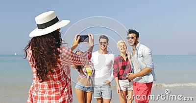 Muchacha que toma la foto del grupo de la gente en la playa en hombre alegre feliz y la mujer del teléfono elegante de la célula  almacen de metraje de vídeo