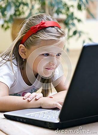 Muchacha que usa la computadora portátil