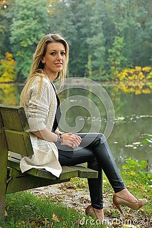 Muchacha rubia que se sienta en banco al lado del lago