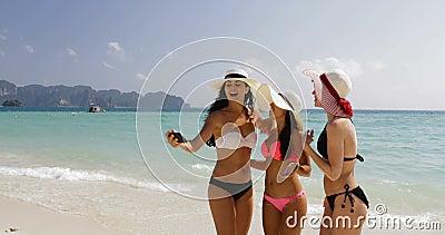 Muchachas en la playa que toma la foto de Selfie en el teléfono elegante de la célula, mujeres alegres en bikini y Straw Hats On  metrajes