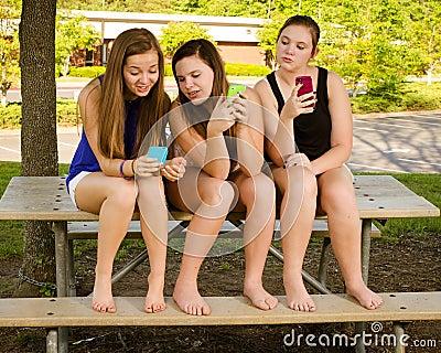 Muchachas Pre-adolescentes que mandan un SMS mientras que cuelga hacia fuera en frente