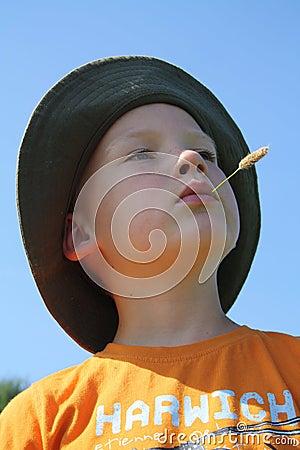 Muchacho con el tallo del maíz en boca