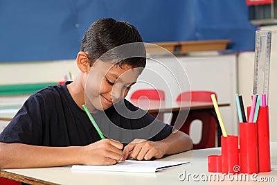 Muchacho de escuela joven 10 que escribe en su escritorio de la sala de clase