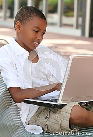 Muchacho del adolescente del afroamericano en el ordenador portátil
