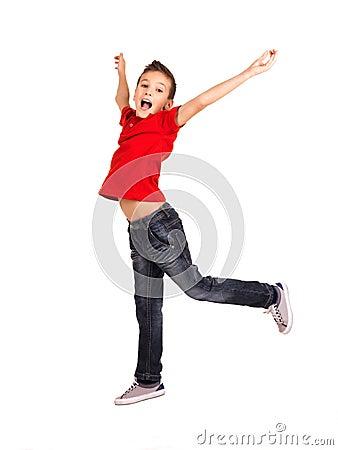 Muchacho feliz que salta con las manos levantadas para arriba