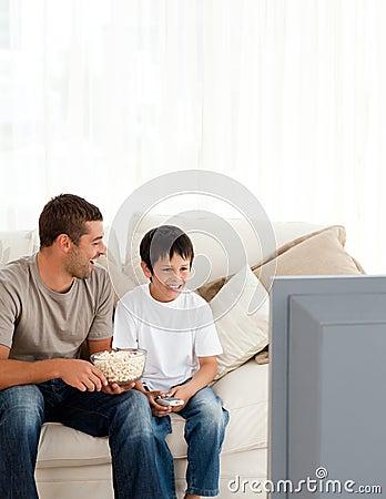 Muchacho feliz que ve la TV con su padre