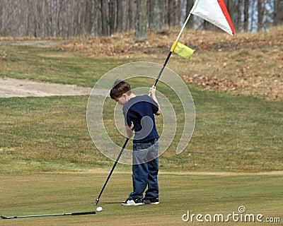 Muchacho joven con el indicador del golf