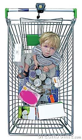 Muchacho joven en carretilla de las compras