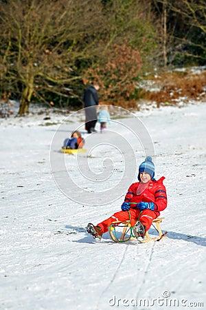 Muchacho joven en el trineo que resbala la colina nevosa, diversión del invierno