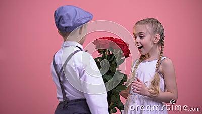 Muchacho joven en la ropa formal que oculta rosas detrás de la parte posterior y que presenta a la muchacha almacen de metraje de vídeo