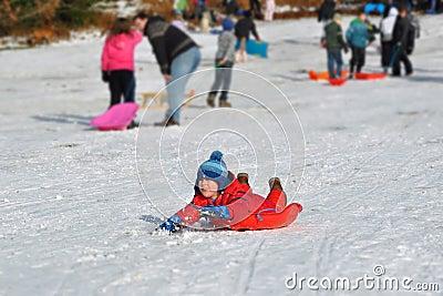 Muchacho joven que resbala la colina nevosa, diversión del invierno