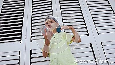 Muchacho lindo en auriculares con el teléfono en sus manos que escucha el baile de la música aislado en el fondo blanco Niño en c metrajes