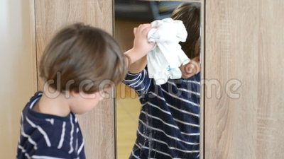 Muchacho que limpia el espejo almacen de video