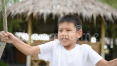 Muchacho que lleva a cabo la cuerda la silla del oscilación y jugar feliz metrajes