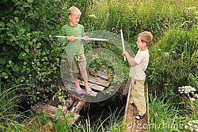 Muchachos con los palillos que luchan para la diversión en los puentes