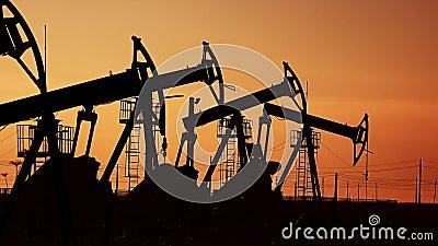 Muchas bombas de aceite en la puesta del sol debajo del cielo rojo en la plataforma industrial colocan con las unidades hidráulic metrajes