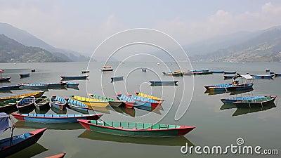 Muchos barcos coloreados de madera vacíos en un lago liso durante el día contra el contexto de un valle de la montaña metrajes