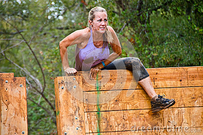 Mud race participant climbing over an obstacle Editorial Photo