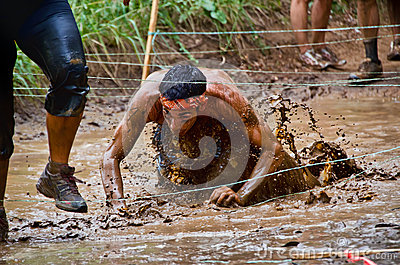 Mud race participant crawling through a mud pit Editorial Photography