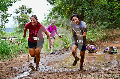 Mud race participants passing through a mud pit Editorial Photo