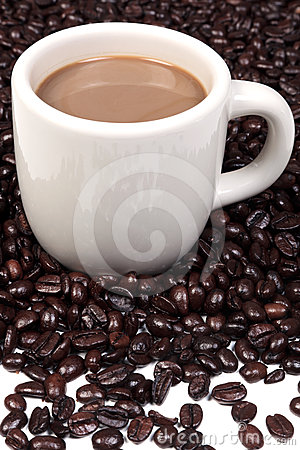 Mug full of hot coffee and beans