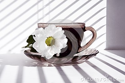 Mug of hot morning coffee and a flower