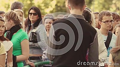 Muitos povos ficam na fila para extasiar no evento do verão segurança multidão Adulto, juventude ensolarado bilhete video estoque