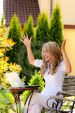 Mujer acertada con una computadora portátil en el jardín